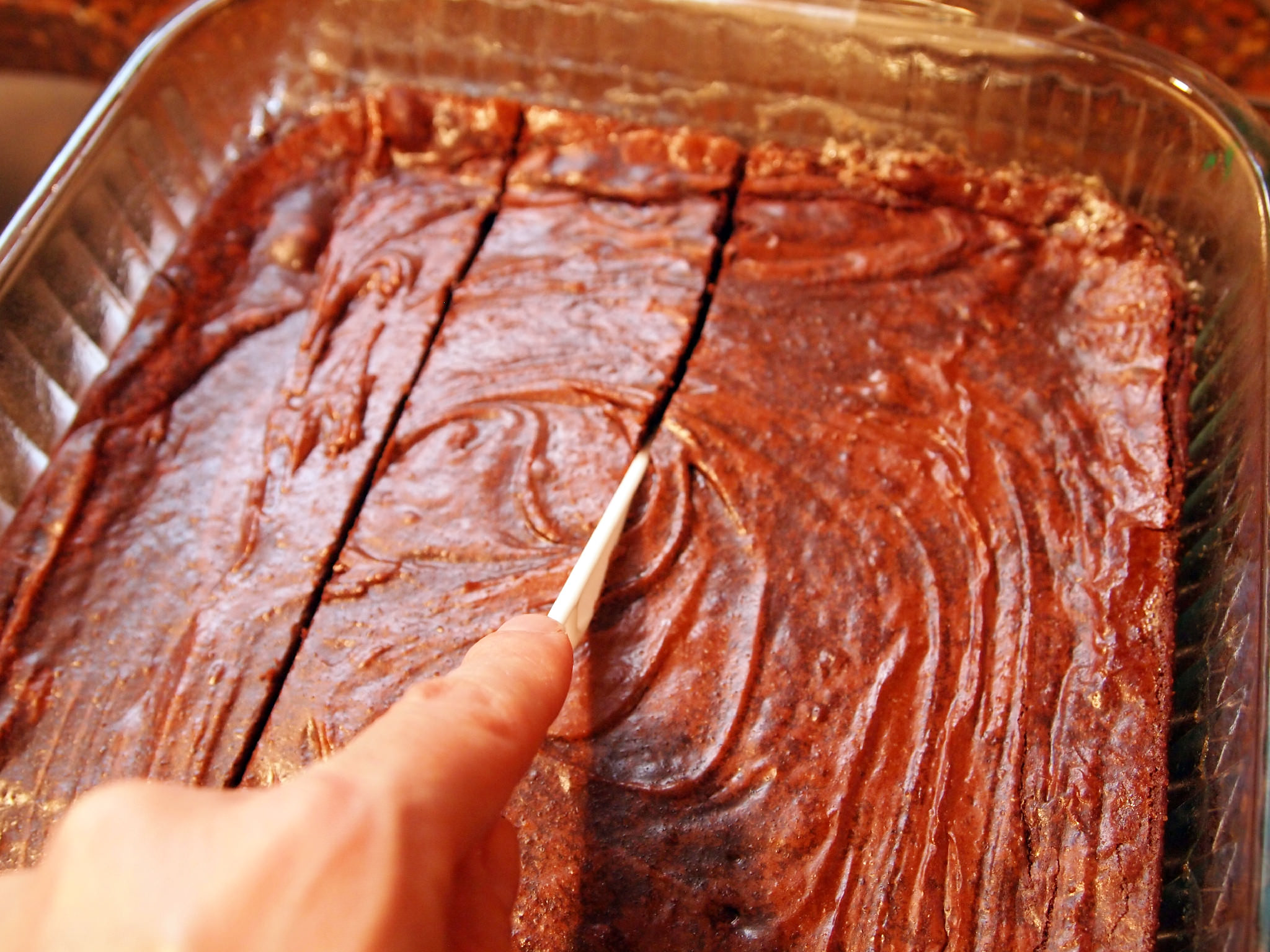 slicing a pan of brownies