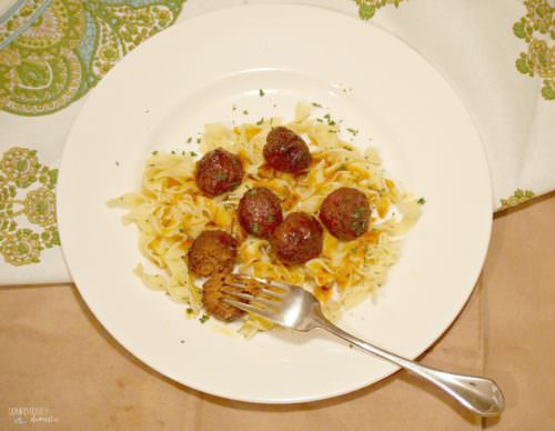 Game Day Meatballs are simmered all day in a crock pot until super tender and bathed in a flavorful sweet & spicy sauce made with grape jelly.   ComfortablyDomestic.com