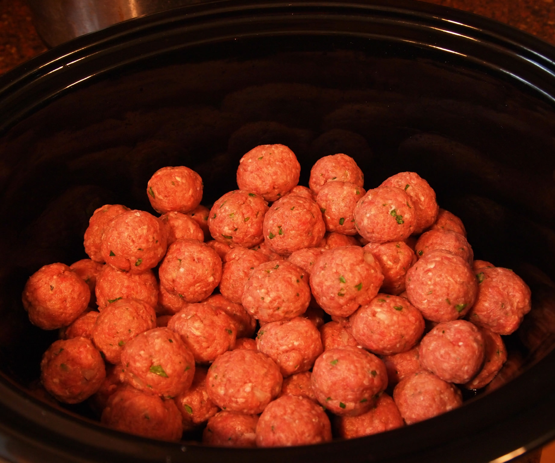 Game Day Meatballs are simmered all day in a crock pot until super tender and bathed in a flavorful sweet & spicy sauce made with grape jelly. | ComfortablyDomestic.com