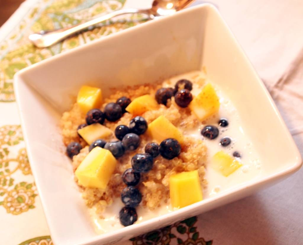 Breakfast quinoa with fresh blueberries and mango is healthy, delicious, and super easy to make! Get the easy hot breakfast cereal recipe from ComfortablyDomestic.com