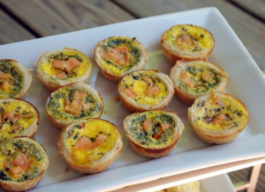 Smoked salmon quiche bites are the perfect appetizer or brunch treat. Two bites of smoked salmon, nestled in flaky pastry along with with herbed eggs, goat cheese, and dill. | ComfortablyDomestic.com