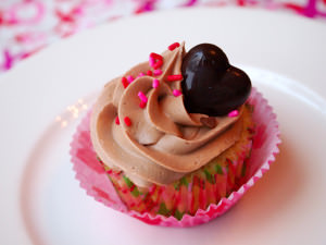 Raspberry filled vanilla cupcakes are the perfect festive touch for your Valentine's Day party! Moist vanilla cupcakes with raspberry filling are topped with creamy milk chocolate buttercream. | ComfortablyDomestic.com