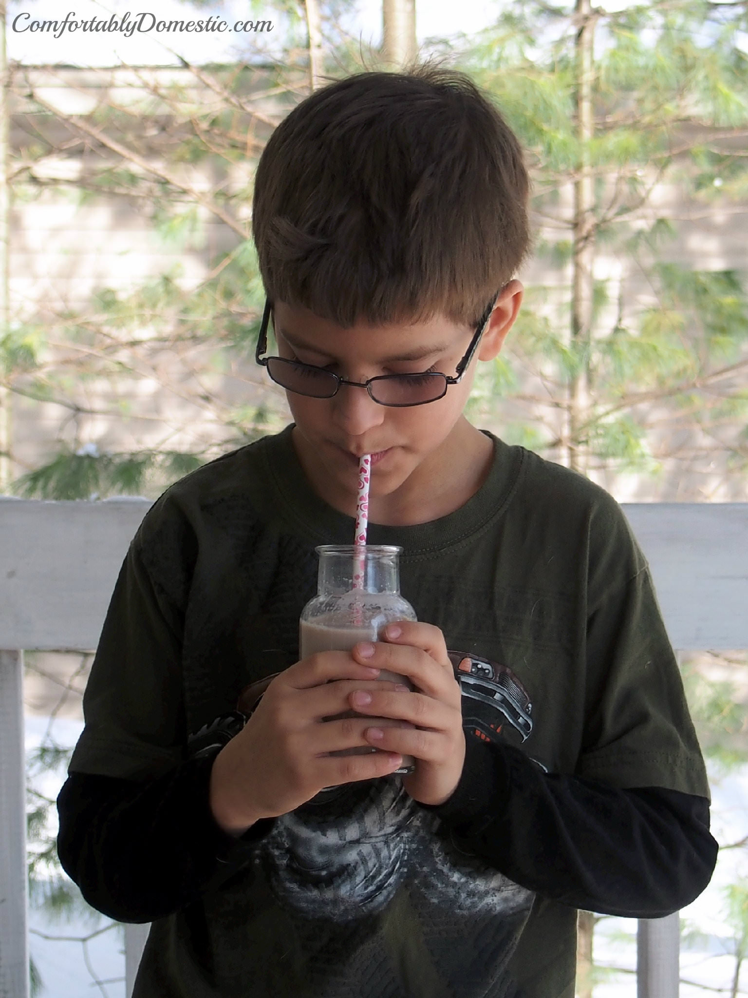boy drinking chocolate milk made with homemade chocolate syrup.