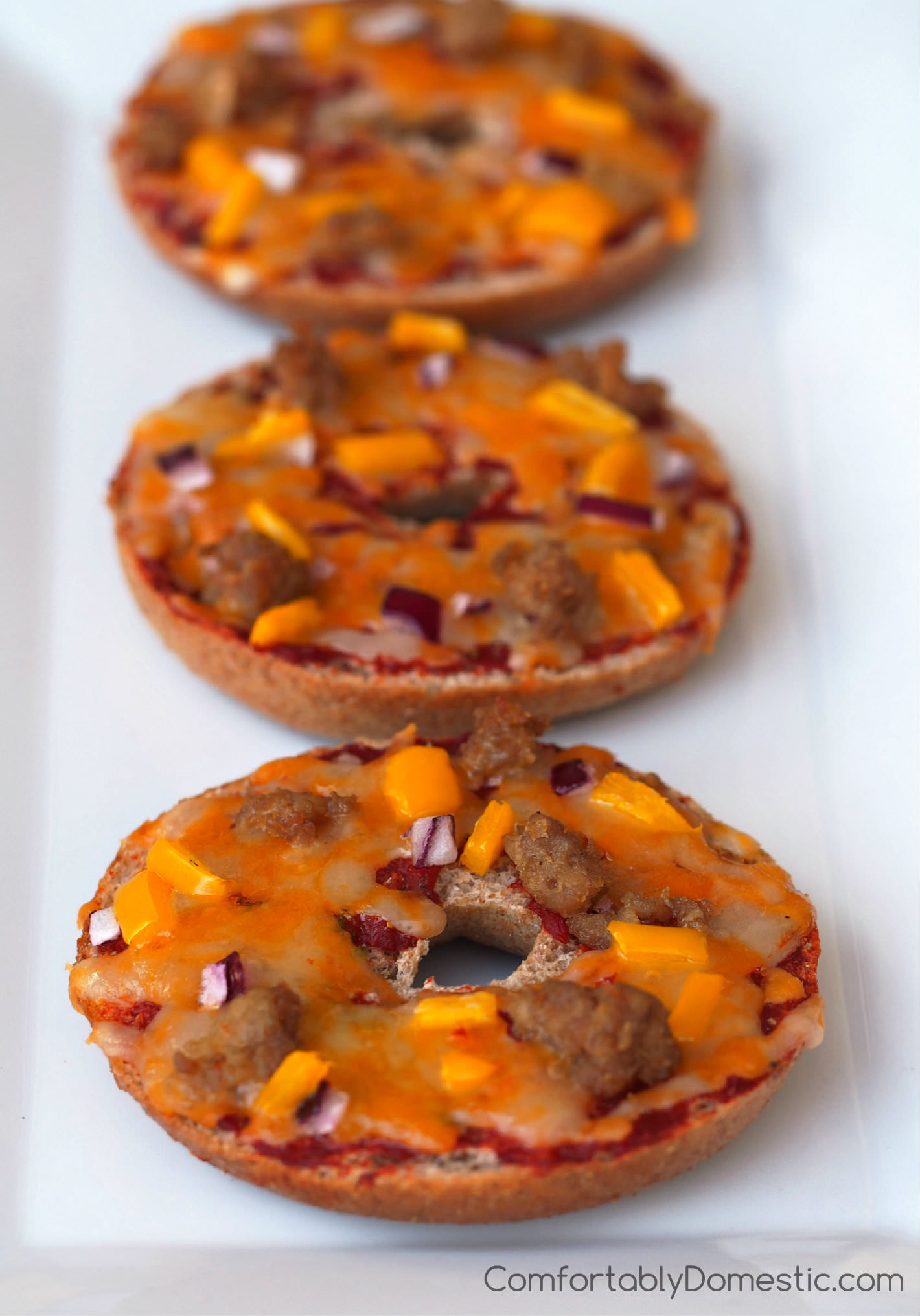 Copy Cat Bagel Bites - Whole grain bagels topped with wholesome toppings like cheddar-jack cheese, lean turkey sausage, and a mix of vegetables for a fun and balanced lunch. Bagel Bites may also be assembled ahead and frozen for a quick after school snack. | ComfortablyDomestic.com