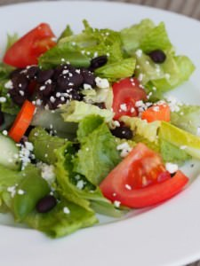 Black beans, crisp greens, fresh vegetables, and Cotija cheese, brightly dressed in a simple lemon vinaigrette. This is a delicious healthy salad recipe!