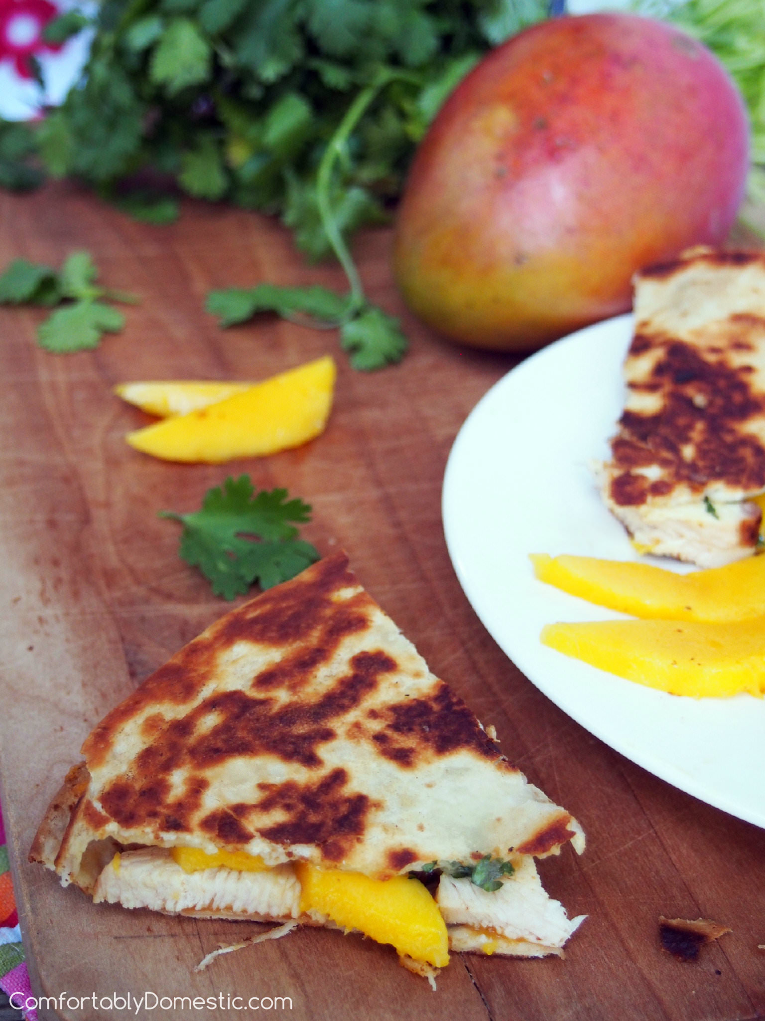 Mango chicken quesadillas start with tender grilled chicken, fresh mango slices, and creamy brie cheese. They're layered and toasted between buttery flour tortillas. They are a great use for leftover chicken, making a healthy lunch or quick snack. | ComfortablyDomestic.com