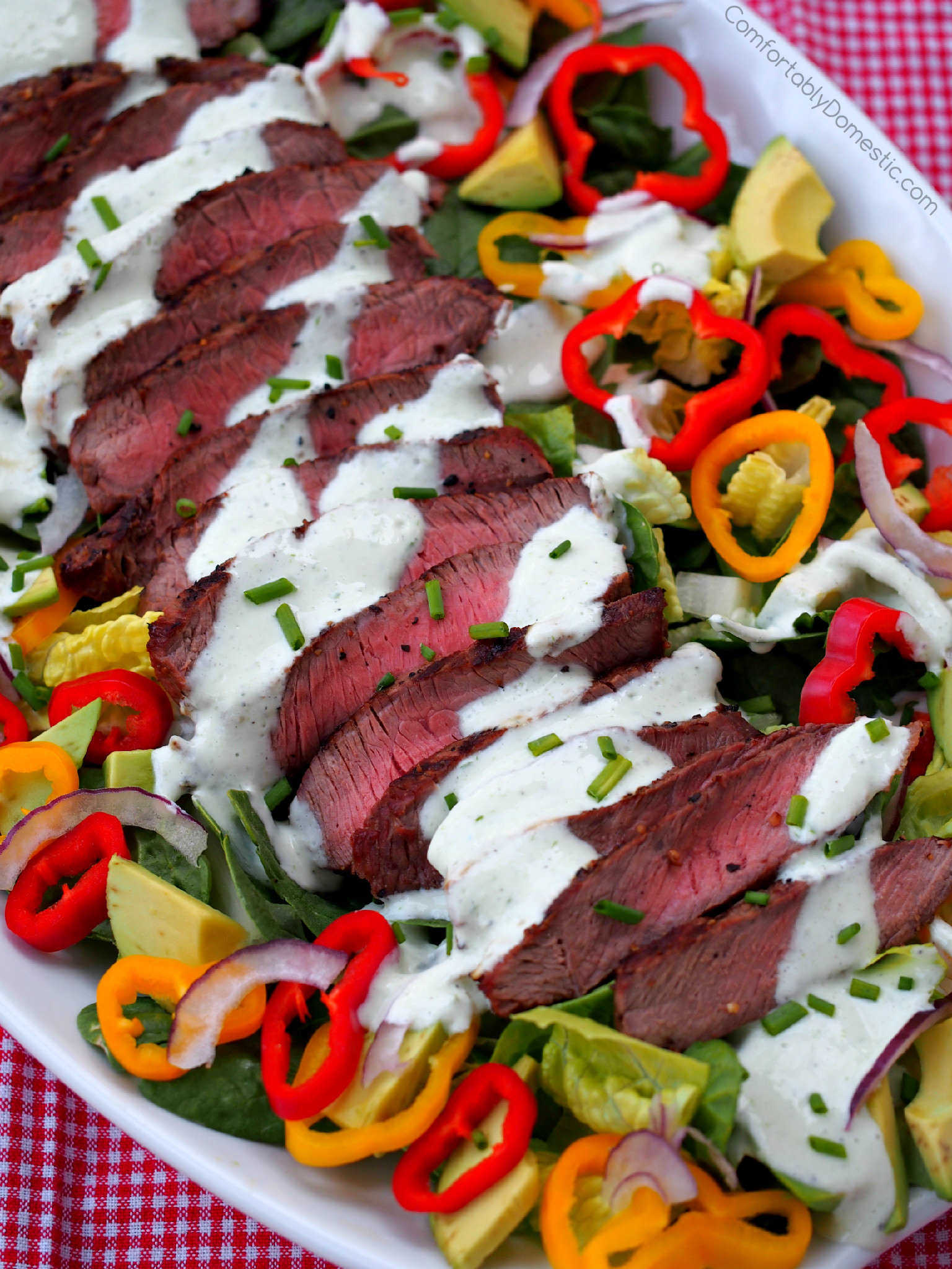 Grilled Steak Salad - Grilled steak sliced over colorful greens, sweet bell peppers, avocado, and thinly shaved red onion Drizzled with healthy, flavorful chive yogurt dressing.   ComfortablyDomestic.com