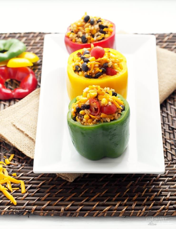 Vegetarian-Stuffed-Peppers-add-Tex-Mex flavor to sweet bell peppers filled with a combination of chewy brown rice, tender black beans, garden fresh vegetables, tangy cheese, and blend of southwest seasonings to make these healthy morsels anything but bland or ordinary.