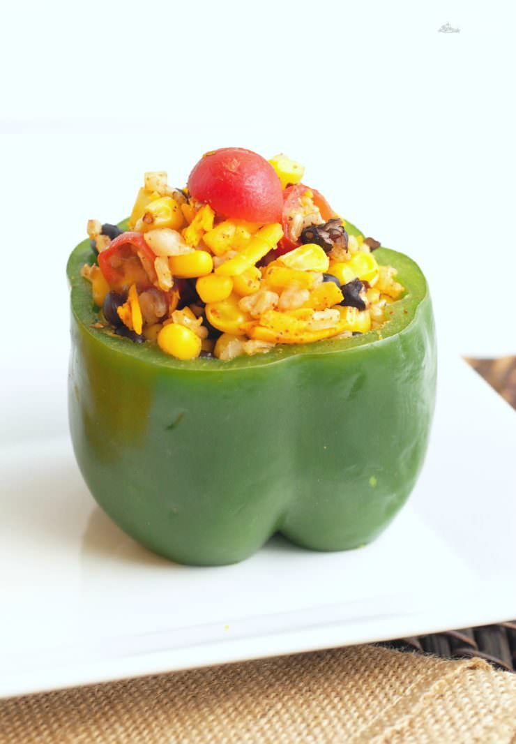 Vegetarian-Stuffed-Peppers-add-Tex-Mex-flavor to sweet bell peppers filled with a combination of chewy brown rice, tender black beans, garden fresh vegetables, tangy cheese, and blend of southwest seasonings to make these healthy morsels anything but bland or ordinary.