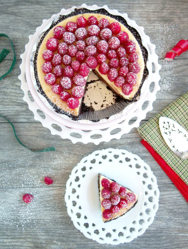Chocolate-Layer-Cheesecake has a rich layer of vanilla cheesecake resting atop a decadent layer of chocolate cheesecake nestled in a chocolate cookie crust. Topped with fresh raspberries and whipped cream, this cheesecake is a showstopper!