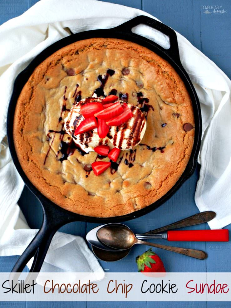 Skillet-Chocolate-Chip-Cookie-Sundae takes all of the iconic comfort of the classic cookie and serves it up in a cast iron skillet. The gloriously warm and gooey cookie is served family style with vanilla ice cream, chocolate syrup, and fresh strawberries.