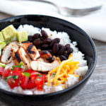 Chicken-Burrito-Bowls nestle perfectly seasoned chicken atop a bed of fluffy lime-cilantro rice along with roasted black beans and all the trimmings for a healthy dinner with loads of flavor. A copy cat recipe of the Chipotle restaurant favorite.