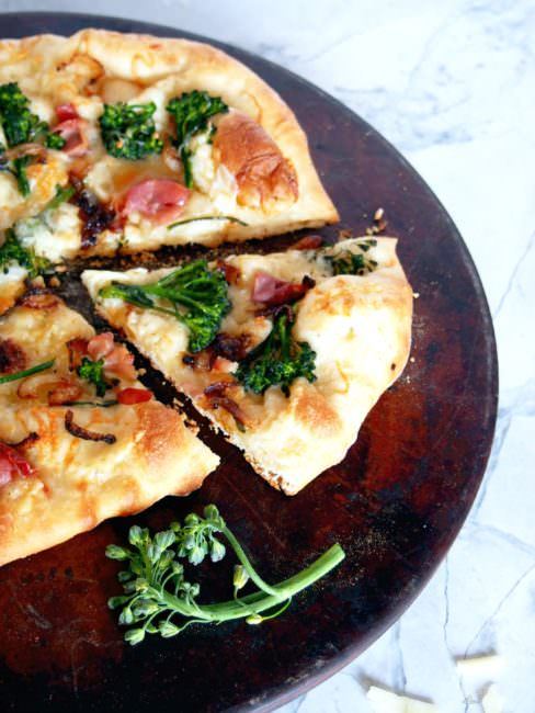 Prosciutto-and-Broccolini-Pizza proves that simple pizzeria style pizza is easily made at home! The chewy, thin crust pizza dough brushed with garlic butter, then topping it salty prosciutto, earthy broccolini, sweet caramelized onions, and shaved Asiago cheese is a taste to behold.