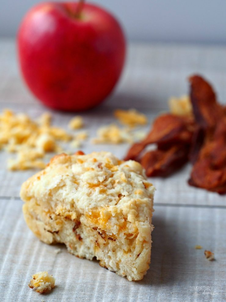 A single Apple Cheddar Bacon Scone with shredded cheese, crisp bacon, and an apple in the background.