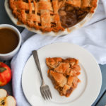 Overhead shot of a slice of caramel apple pie on a white plate with a fork.................