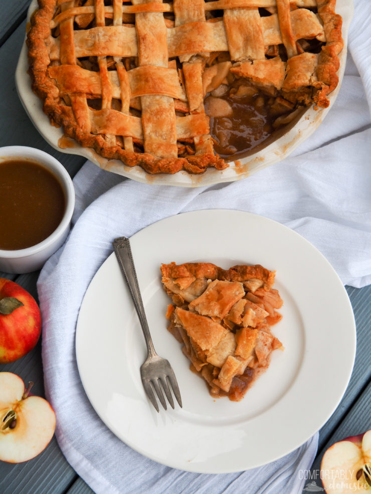 An overhead shot of a slice of caramel apple pie with a fork on the plate.