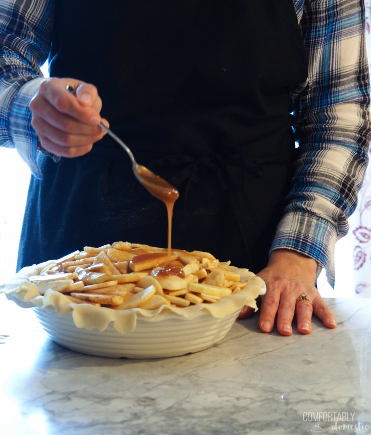 a hand drizzling caramel over the apples in the filling of a caramel apple pie.