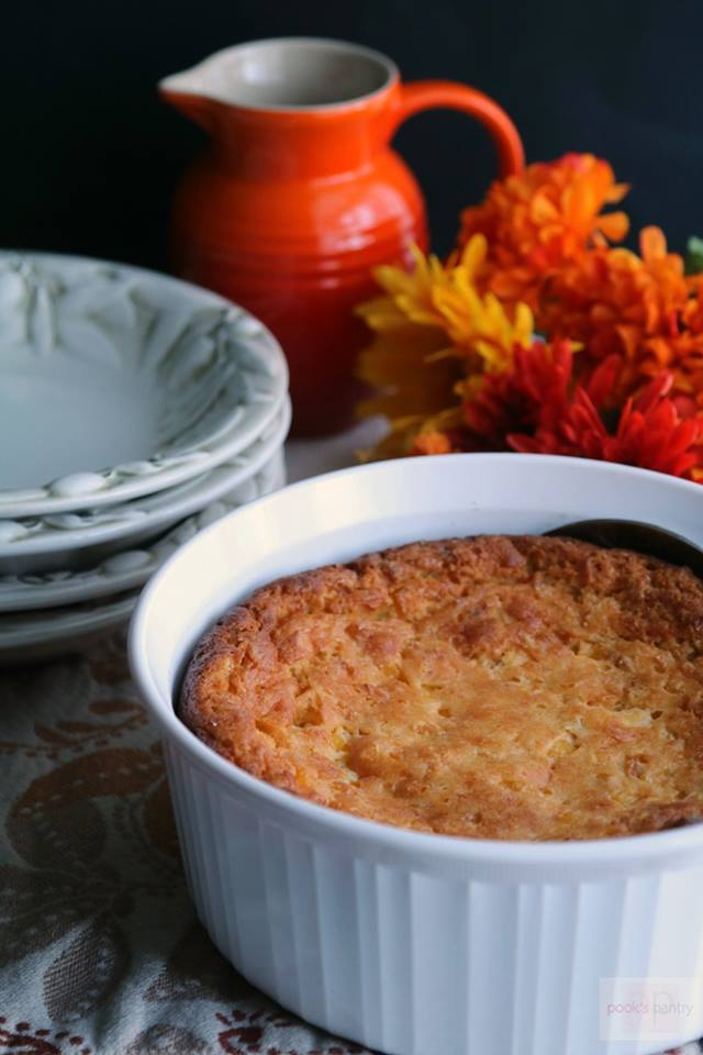 corn-casserole-in-white-bowl-with-orange-flowers-in-background