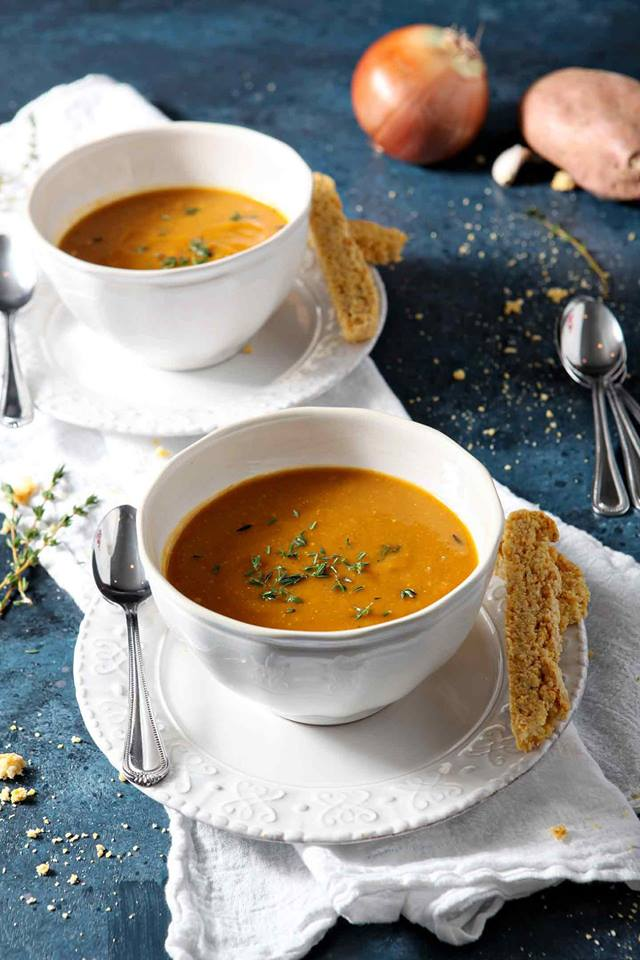 two-white-bowls-filled-with-vegetarian-sweet-potato-bisque-soup-with-spoons-and-bread