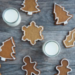 Overhead view of gingerbread cut out cookies with two glasses of milk.