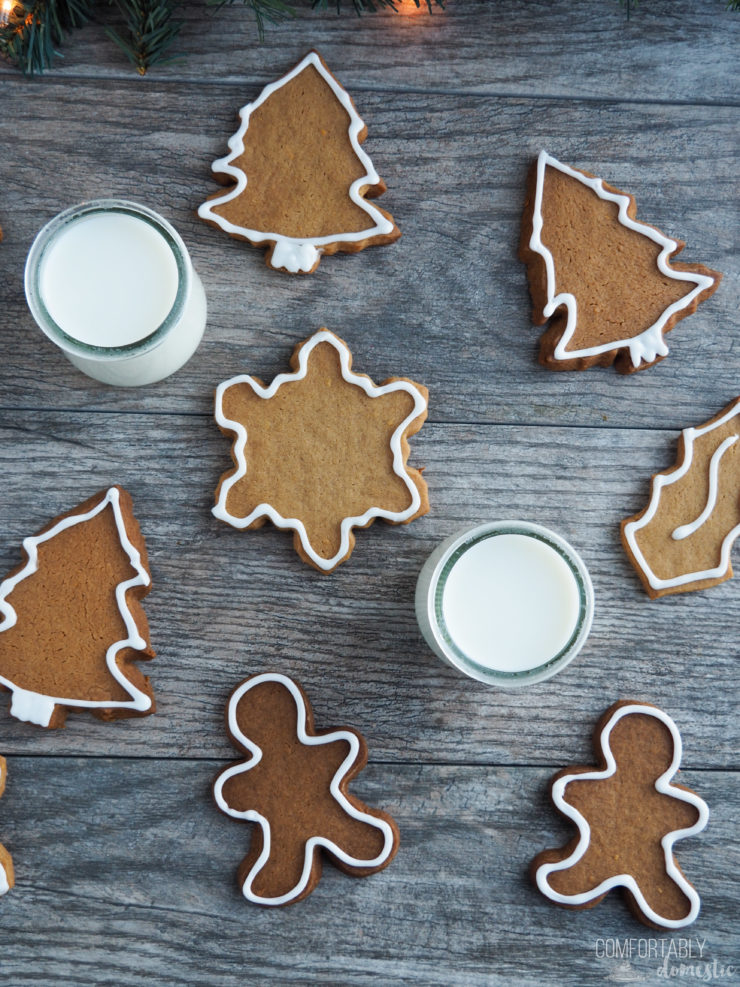 Overhead view of a scattering of gingerbread cut out cookies with two glasses of milk.