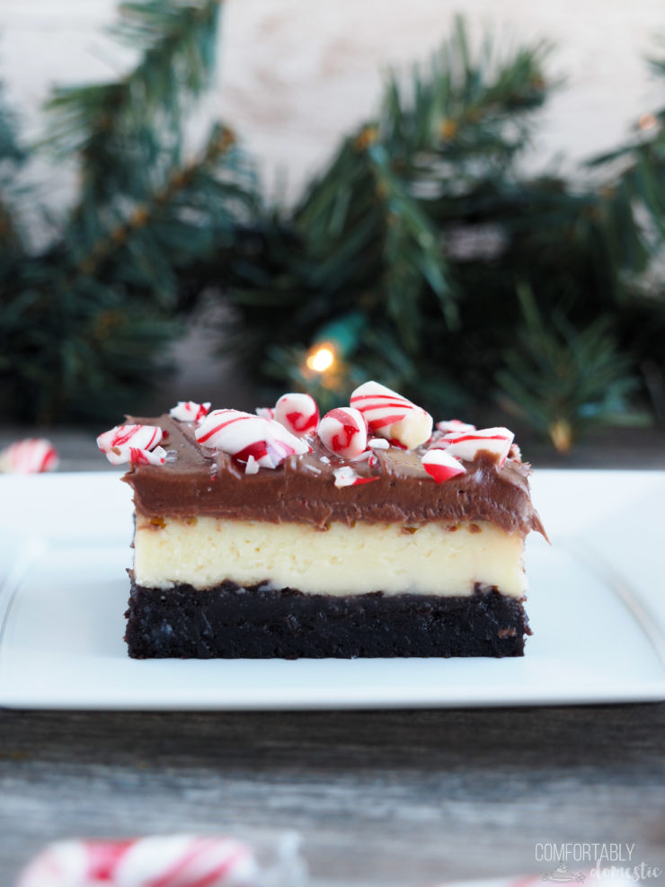 Close up photo of a layered peppermint cheesecake brownie on a white plate with pine garland in the background.