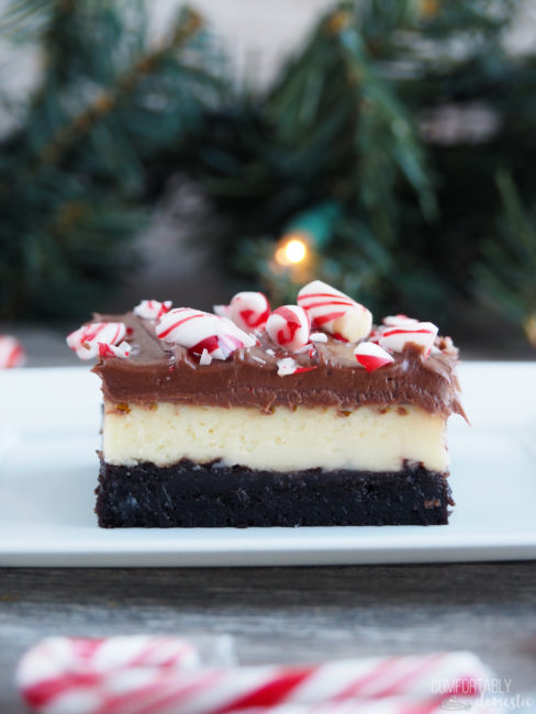 Close up of a layered peppermint cheesecake brownie on a white plate with pine garland and twinkle lights in the background.