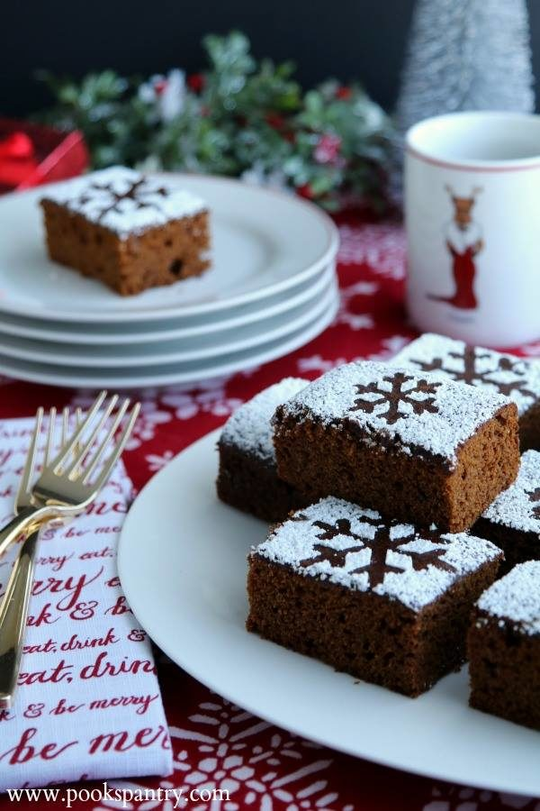 Plate of stacked gingerbread cake squares with stenciled powdered sugar snowflakes on top.
