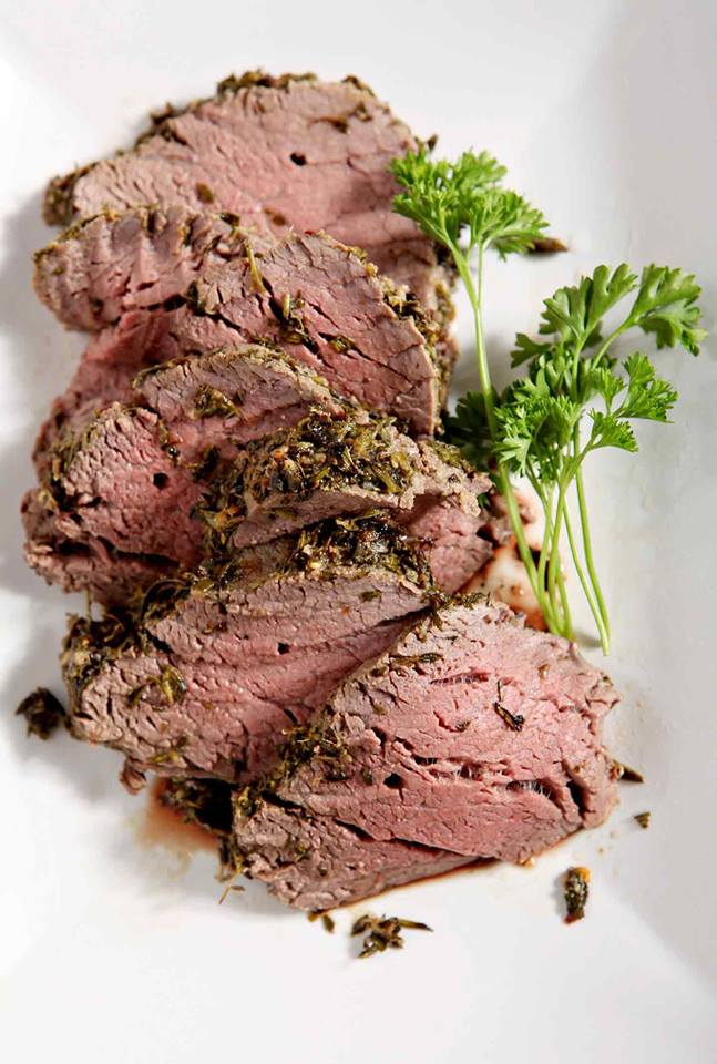 slices of herb crusted beef tenderloin on a white plate