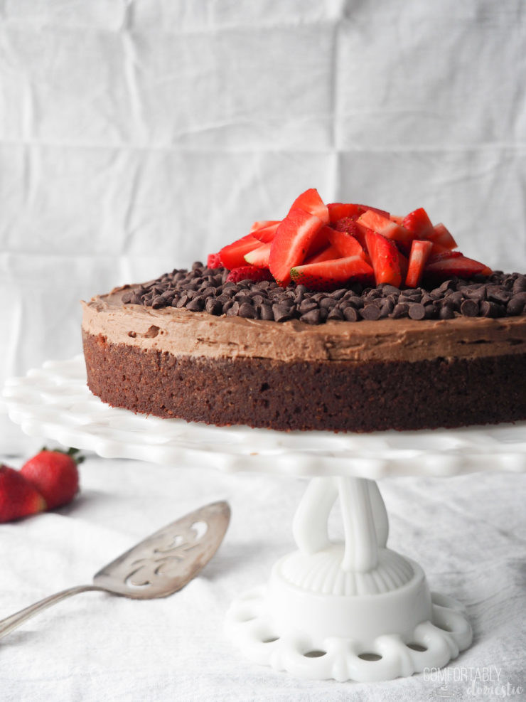 Gluten-free-fudge-cake-frosted-with-chocolate-chips-and-strawberries on a white pedestal plate.