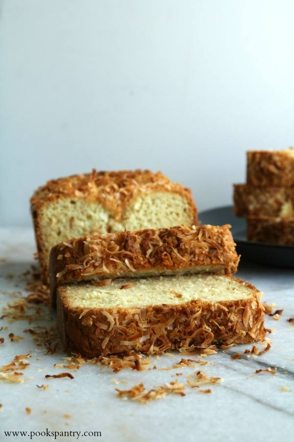 Slices of coconut bread with toasted coconut flakes on top, resting on a white background.