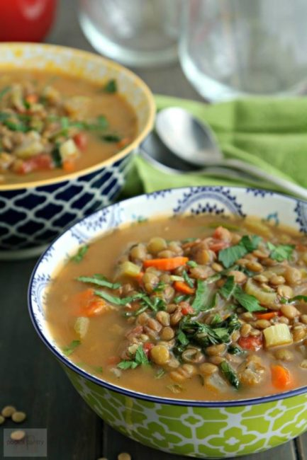 Two bowls of lentil soup with parsley sprinkled on top.