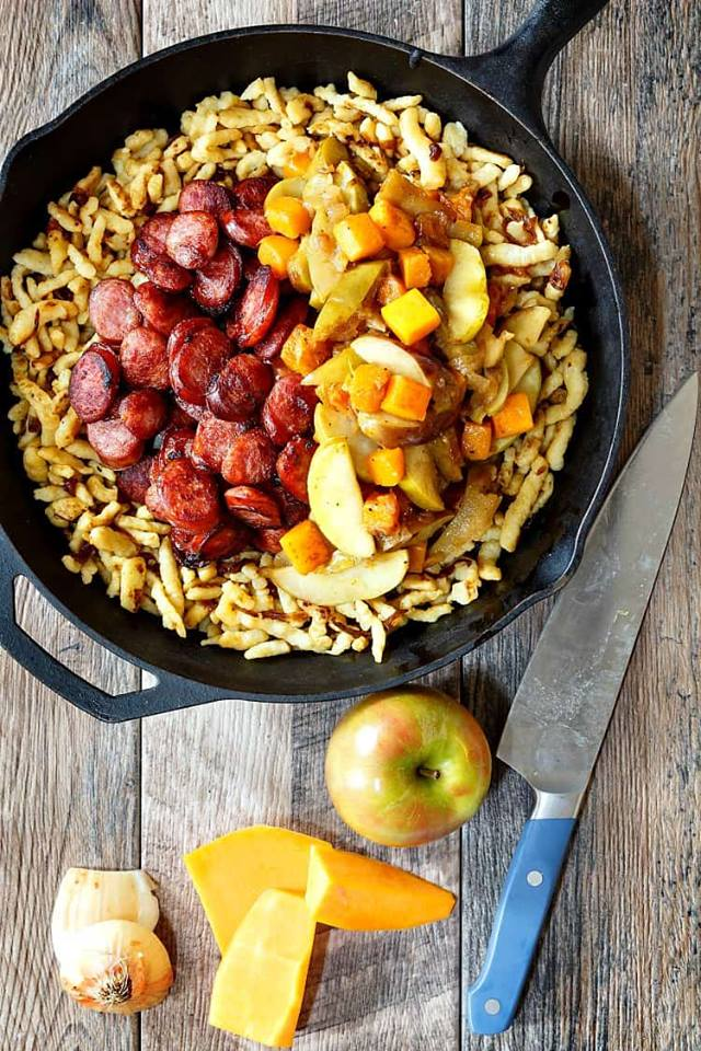 A cast iron skillet with spaetzle dumplings, sliced sausage, diced apples, and cubes of butternut squash.