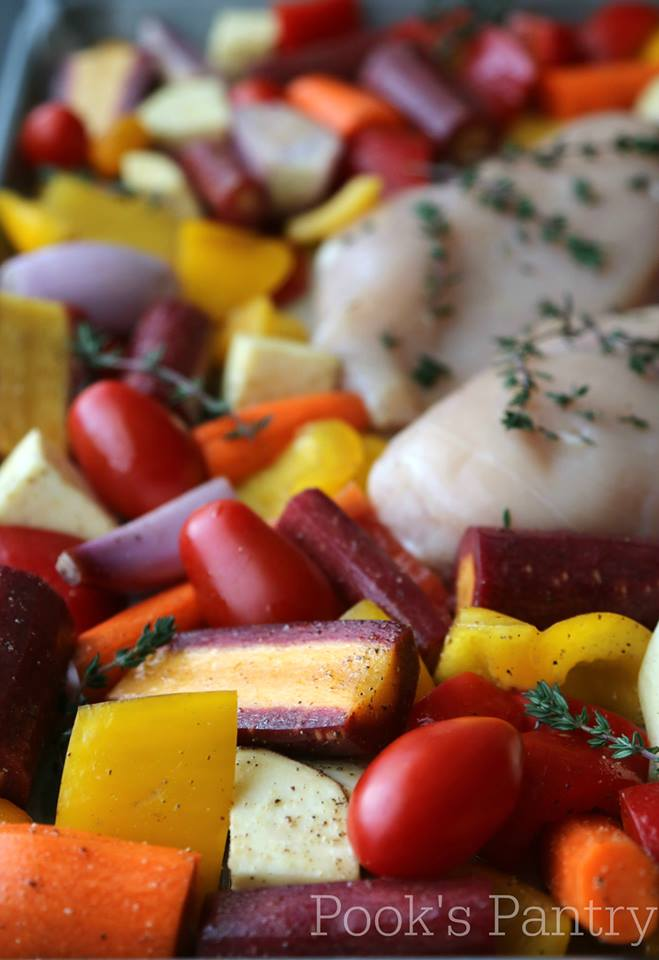 Overhead photos of multicolored carrots, tomatoes, sweet peppers, and boneless skinless chicken breasts on a sheet pan.