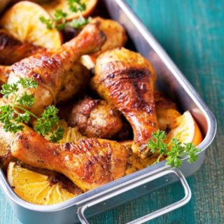baked chicken drumsticks in a stainless steel roasting pan on blue background