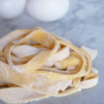 a pile of homemade egg noodles on white marble with two eggs in the background.