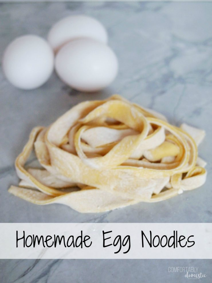 homemade-egg-noodles on white marble with eggs in the background