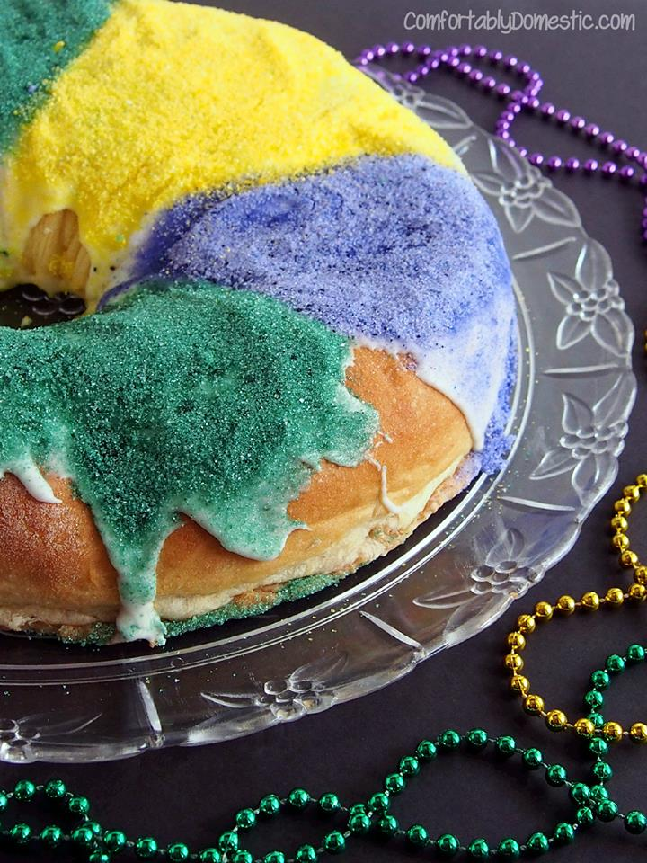 close up photo of Mardi Gras King Cake covered in green, purple, and yellow sugar and beads in the background.