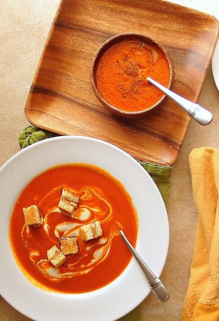 tomato soup in a white bowl with croutons on top.
