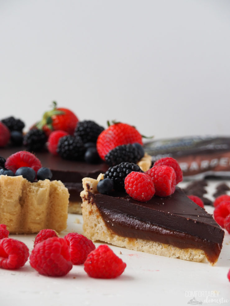 Slice of a Salted Caramel Chocolate Tart with fresh berries on top and scattered around it.