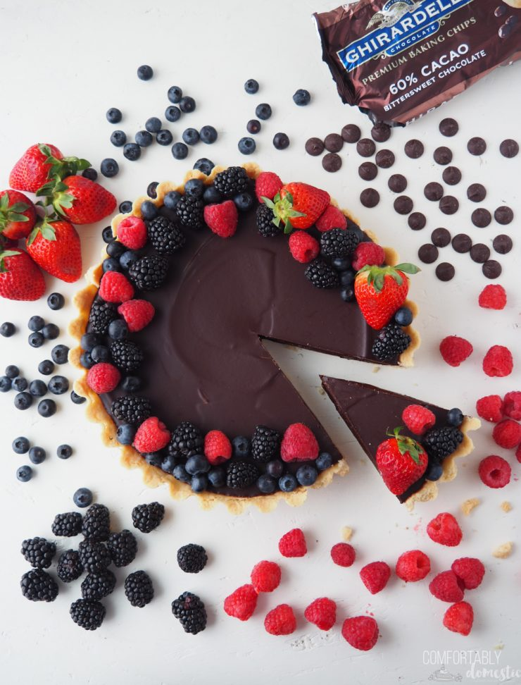 Overhead photo of a Salted Caramel Chocolate Tart on a white background with fresh blueberries, raspberries, strawberries, black berries, and chocolate chips scattered around it.