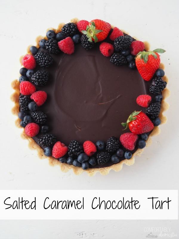 Overhead photo of a Salted Caramel Chocolate Tart garnished with fresh blueberries, strawberries, raspberries, and blackberries on a white background.