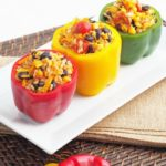 Stuffed red, yellow, and green bell peppers on a white plate.