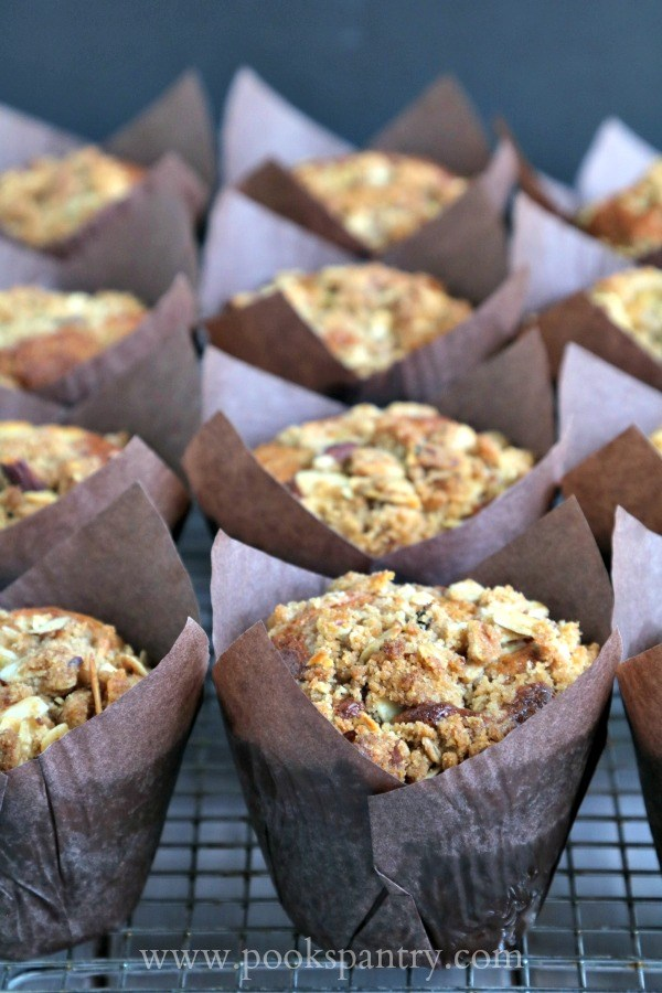 a dozen banana muffins in brown tulip style muffin wrappers.