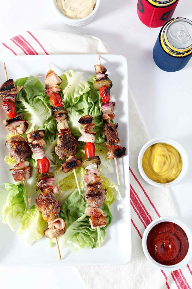 cheeseburger-kebabs on a bed or romaine lettuce on a white platter.
