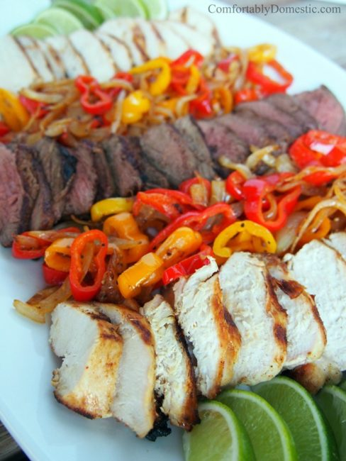 sliced steak and chicken on a white platter with lime wedges and roasted sweet peppers and onions.