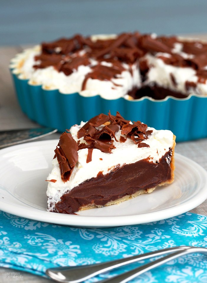 slice of chocolate french silk pie on a white plate with the whole pie in a blue pan in the background.