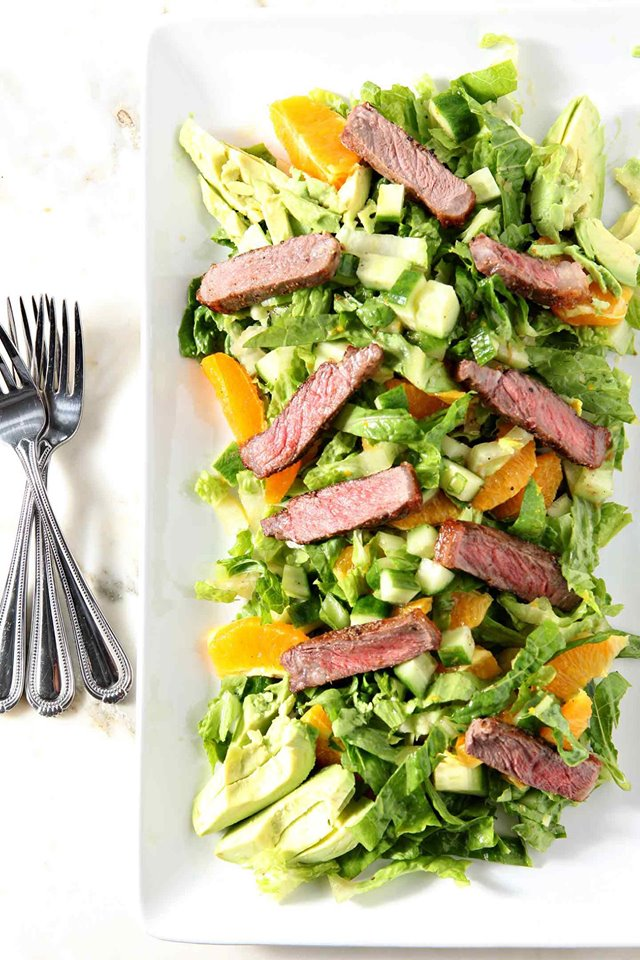 orange steak salad on a white plate