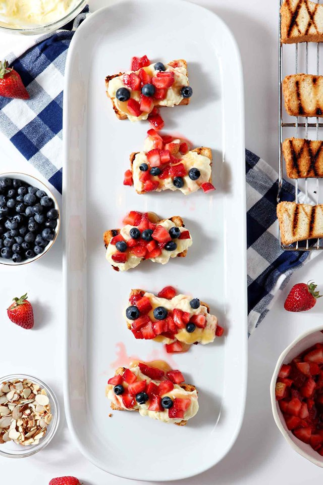 Patriotic Strawberry Bruschetta is strawberry and blueberries atop goat cheese on toast rounds on a white platter.