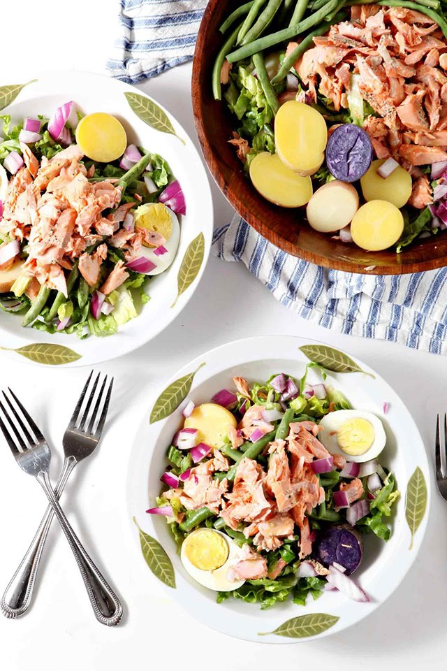 three bowls of salmon niscoise salad in white bowls with a blue striped napkin
